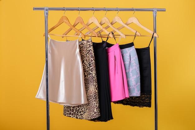 オレンジのラックのハンガーに女性のカラフルなスカート。