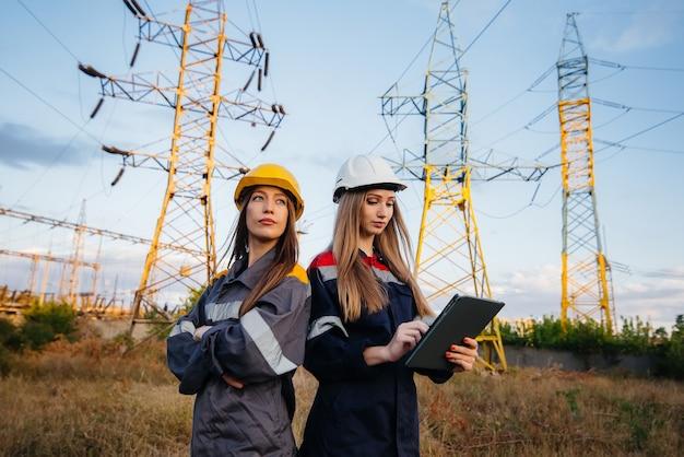 女性が機器や電力線の検査を行う