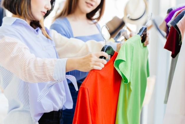 여성은 패션 샵에서 새 옷을 사는 것과 좋은 가치를 위해 두 셔츠 색상과 크기를 비교하여 결정을 내렸다고 생각합니다.