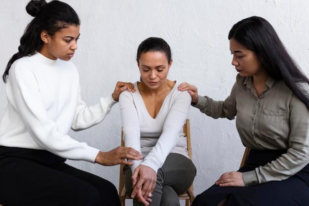 그룹 치료 세션에서 슬픈 사람을 위로하는 여성