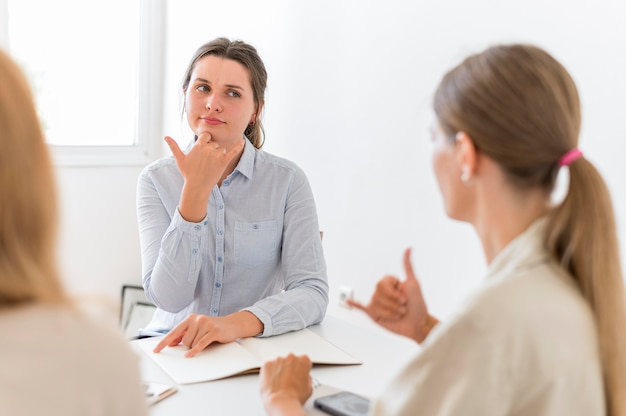 Женщины разговаривают за столом, используя язык жестов