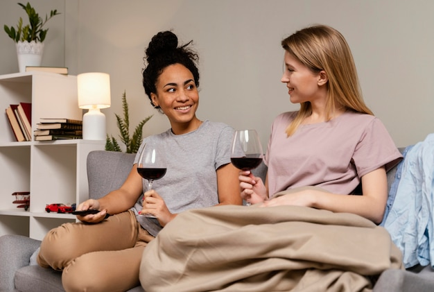 Women on couch watching tv and drinking wine