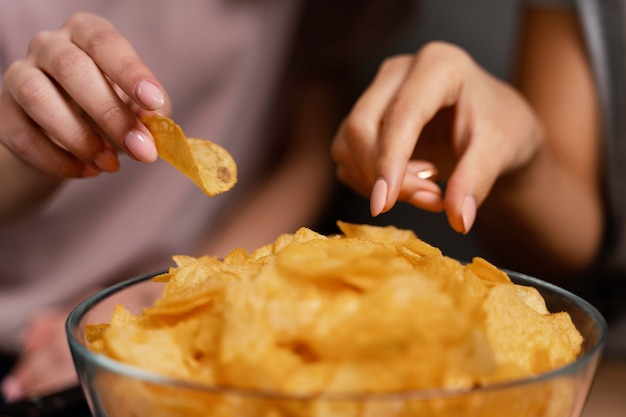 Women on couch watching tv and eating chips close up