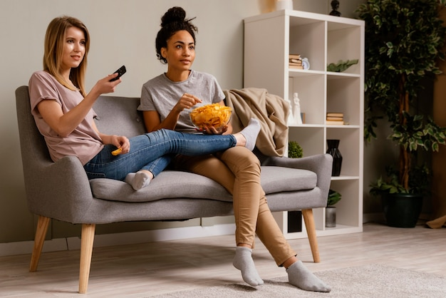 Women on couch watching tv and eating chips