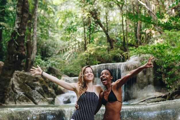 Women couple enjoying the waterfall