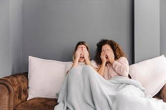 Women covering eyes during scary film