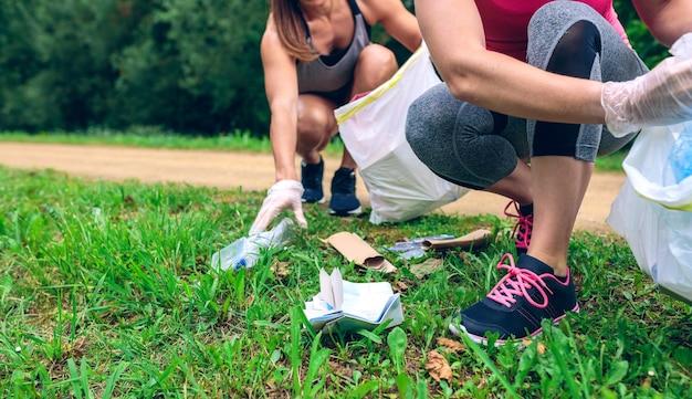 Women crouching with bag picking up trash doing plogging