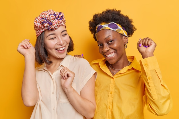 Women dance carefree enjoy favorite music keep arms raised up wears shirts smile happily isolated on vivid yellow
