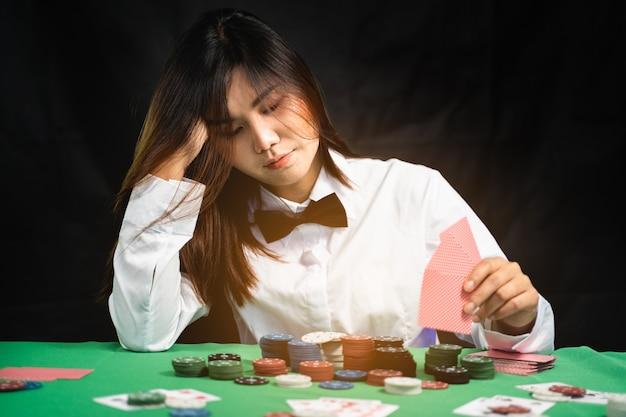 Women dealer or croupier shuffles poker cards in a casino