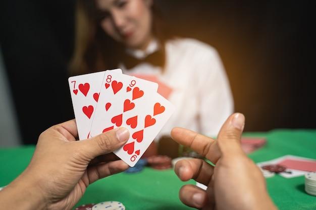 카지노에서 포커 카드를 셔플하는 여성 딜러 또는 크루 퍼