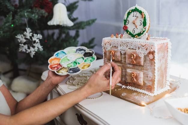 Women decorates ginger cookies christmas chest of drawers at home. woman draws paints on honey gingerbread cookies. close-up