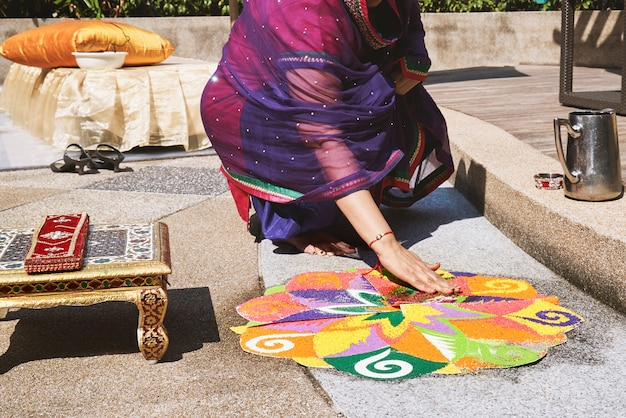 Women decorating the traditional rice art (rangoli) on the floor for indian wedding