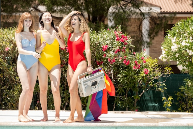 Women of different ethnicities in swimsuits having fun in the pool. gay pride concept