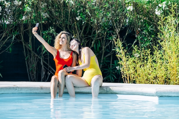 Women of different races in bikinis having their photo taken at the edge of a swimming pool