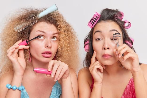 女性は隣同士に立ってメイクアップしますヘアローラーを適用しますマスカラはまつげカーラーを使用して特別な機会のために準備します美しく見えたいです。