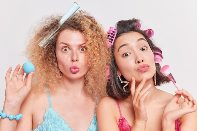 女性は化粧ブラシを保持し、スポンジは髪型のドレスを互いに密接に立たせ、白で隔離された日付の準備をします