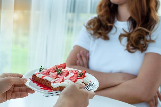 Женщины не едят сладости и десерты. руки отправляют тарелку с клубничным хлебом, но женщина выказывает сниженное намерение похудеть и похудеть. концепция диеты