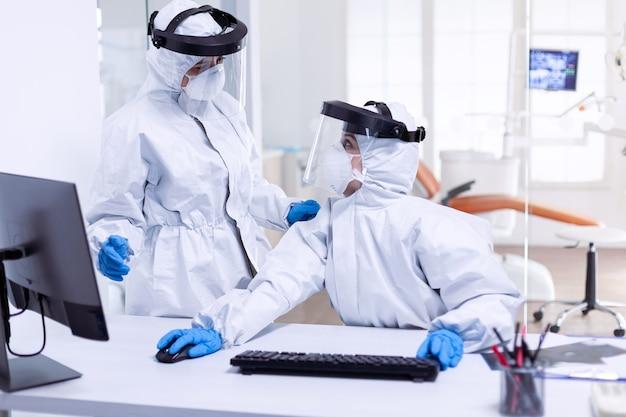 歯科受付でcovid-19とパンデミックと戦うための防護服を着た女性医師。安全対策として、歯科受付でコロナウイルスのパンデミックに対する保護具を着用している医療チーム。