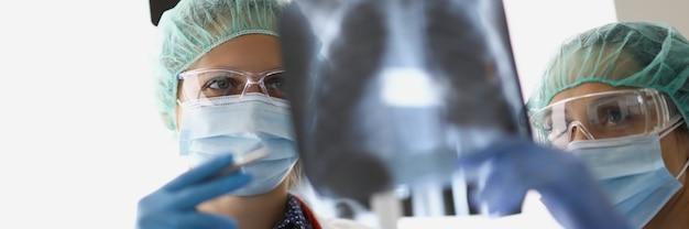 Женщины-врачи стоят в офисе и смотрят на рентгеновские снимки легких.