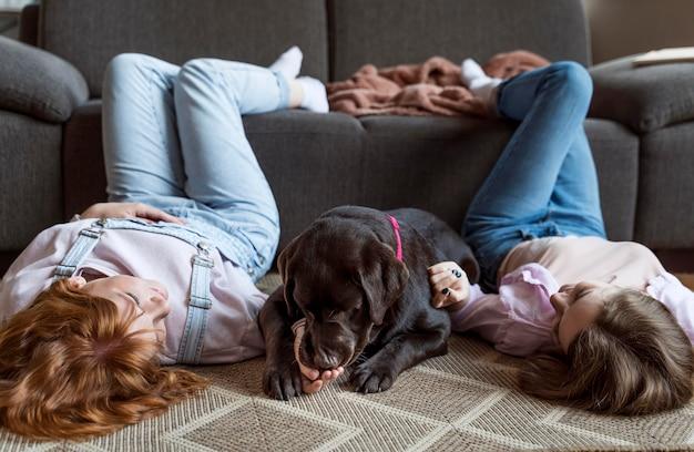Donne e cane posa sul pavimento