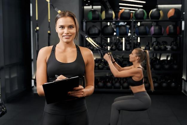 현대 체육관에서 trx 시스템으로 운동을하는 여성