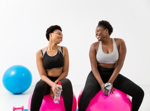 Женщины делают упражнения на фитнес-мяч