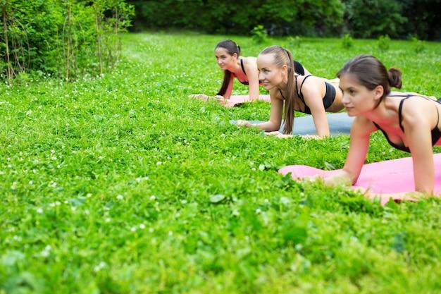 Женщины делают упражнения на открытом воздухе