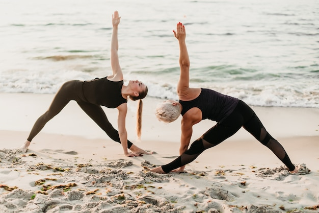 Women doing fitness exercise in sync posing in yoga asana on the beach near sea