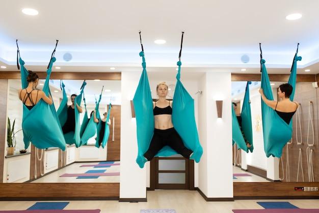 ハンモックでフライヨガストレッチ運動をしている女性