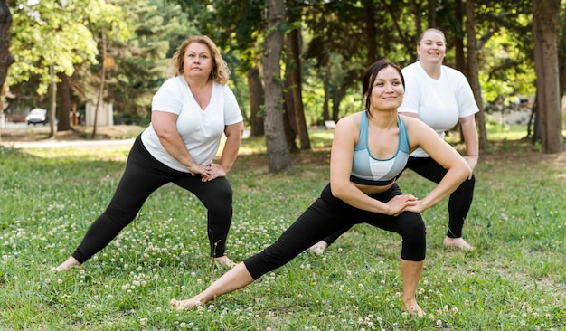 Women doing lateral lunges in the park