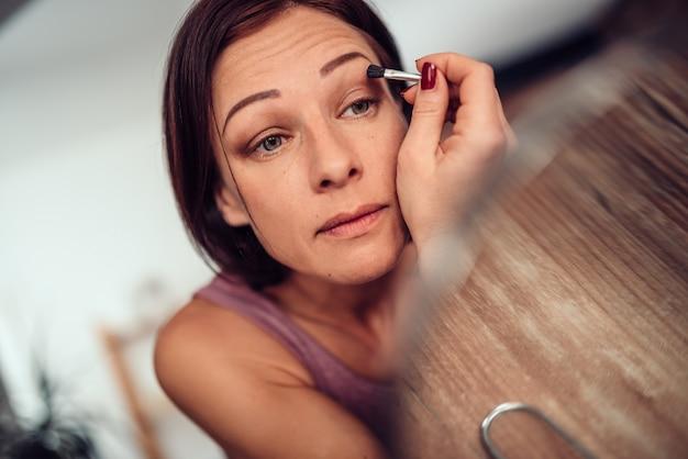 Women doing makeup eyebrow