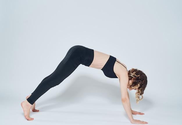 腕立て伏せをしている女性明るい部屋で、スポーツ瞑想ヨガのアーサナ