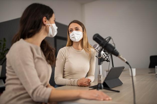 Donne che fanno radio con maschere mediche