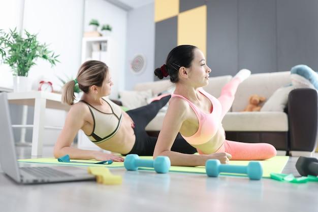 自宅の床でスポーツ運動をしている女性。オンライントレーニングコースのコンセプト