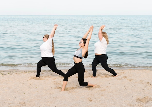 Women doing stretch exercises next to the sea