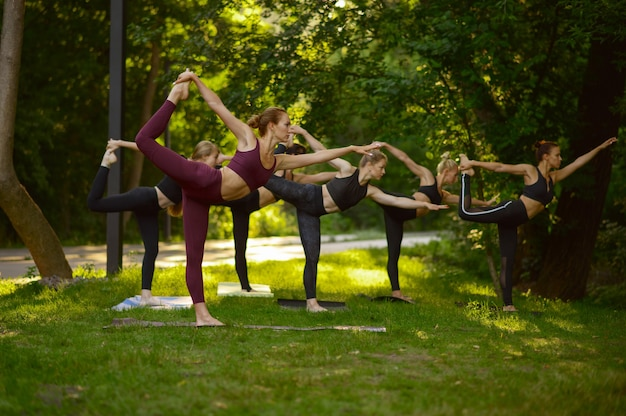Women doing stretching exercise, group yoga training on the grass. meditation, class on workout outdoors, relaxation practice