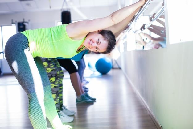 체육관에서 금속 난간을 사용하여 스트레칭을 하는 여성