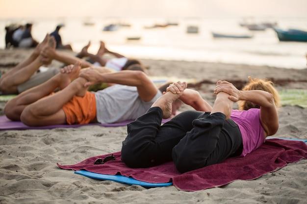 Женщины делают упражнения йоги или поддерживают позу голубя на пустом пляже индийского океана на маврикии