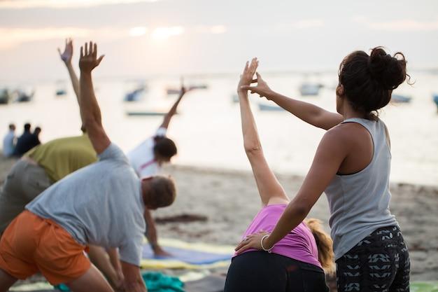 モーリシャスのインド洋の空のビーチでヨガの練習やサポートされている鳩のポーズをしている女性