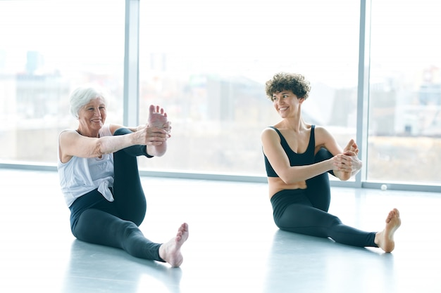 Women doing yoga next to a large window
