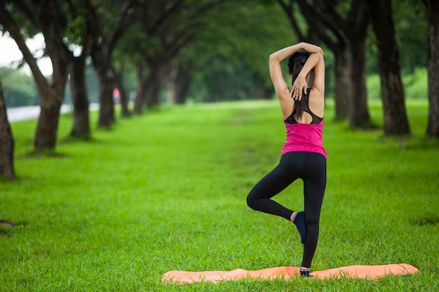 Women doing yoga in park - image