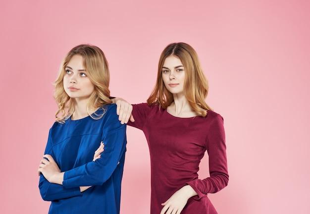 Women in dress friendship emotions fashion glamor pink background. high quality photo