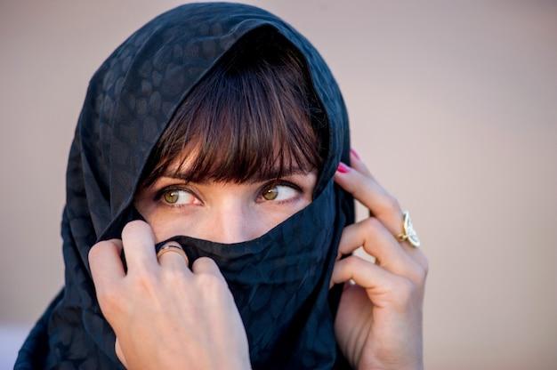 夕日の背景に中東の方法のポーズを着た女性。