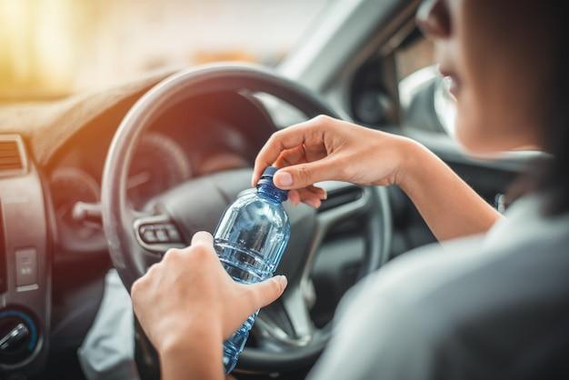 女性は朝の運転中に水を飲みます。