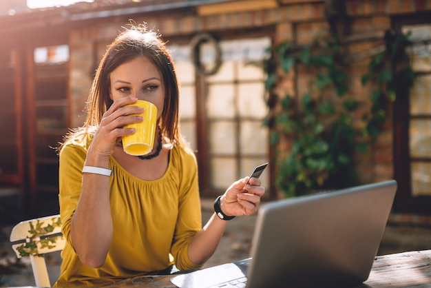 Women drinking coffee at backyard patio and using credit card