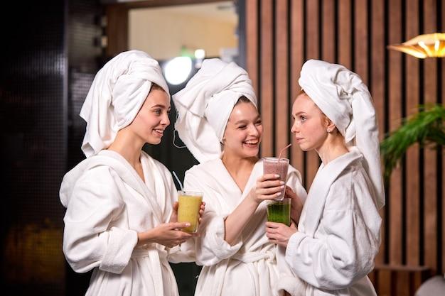 스파 트리트먼트 후 수분이 많은 해독 주스 음료를 마시고, 휴식을 취하고, 미용 절차를 즐기고, 흰 가운을 입고, 휴식을 취하고, 이야기하고, 스파 트리트먼트 개념을 가진 여성
