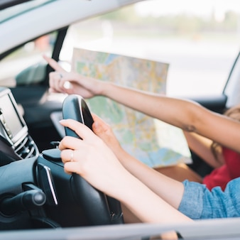 Women driving car with map