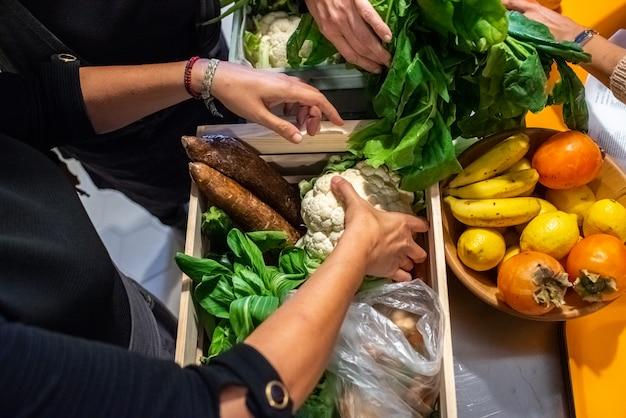 ビーガン料理のコース中の女性は料理のための材料を準備しています。