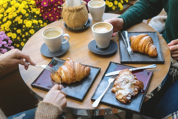 Women eating croissants in a coffee shop with cappuccino.