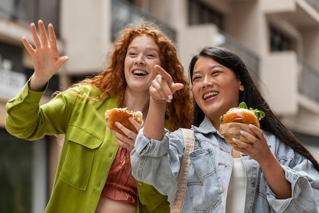 外でおいしいハンバーガーを食べる女性